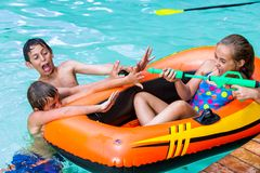 Kinder, die Spaß mit Wasserwerfer haben. Stockfotos