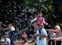 Kinder, die Spaß und mit Seifenblasen fangen und haben lizenzfreies stockbild