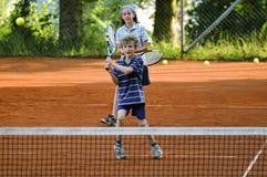 Kinder, die Spiel von Tennis spielen stockfotografie