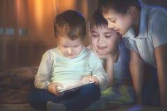 Kinder, die Spiele auf Tabletten-PC spielen Drei kleine Jungen mit Tablet-Computer lizenzfreie stockfotos