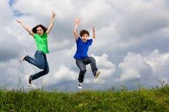Kinder, die, Springen im Freien laufen Stockfotos