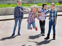 Kinder, die springendes Spiel des Springseils spielen Stockfoto