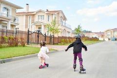 Kinder, die in Straße reiten lizenzfreies stockbild