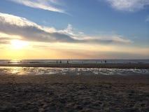 Kinder, die am Strand bei Sonnenuntergang spielen Stockbild