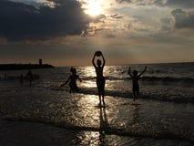 Kinder, die am Strand bei Sonnenuntergang spielen Lizenzfreies Stockbild