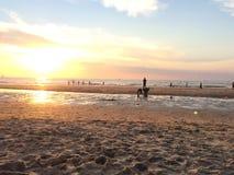 Kinder, die am Strand bei Sonnenuntergang spielen Stockfoto