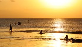 Kinder, die am Strand mit Fischerboot in Bali, Indonesien während des Sonnenuntergangs am Strand spielen lizenzfreies stockfoto