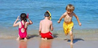 Kinder, die am Strand spielen lizenzfreie stockbilder