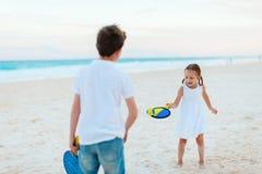 Kinder, die Strandtennis spielen Stockbilder