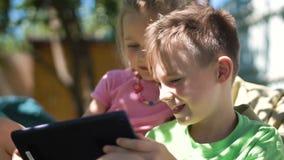 Kinder, die Tablette im Hinterhof genießen stock footage