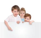 Kinder, die unbelegtes weißes Meldung-Zeichen anhalten lizenzfreies stockfoto