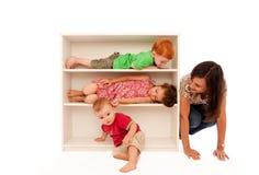 Kinder, die Verstecken mit Mama spielen Stockbild