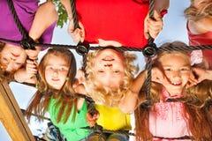 Kinder, die vom Netz auf Spielplatz hängen Stockfotografie