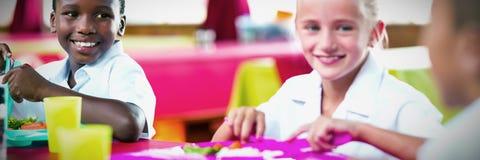 Kinder, die während der Abschaltzeit in der Schulcafeteria zu Mittag essen stockbilder