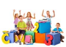 Kinder, die am Würfel sitzen Stockbilder