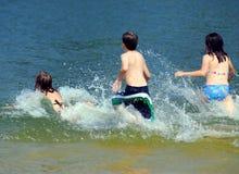 Kinder, die in Wasser laufen Lizenzfreie Stockfotografie