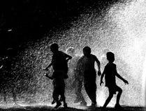 Kinder, die in Wasser laufen Lizenzfreie Stockfotos