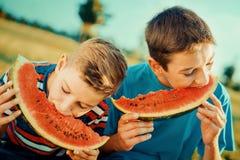 Kinder, die Wassermelone im Park essen stockfotos