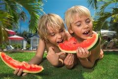 Kinder, die Wassermelonen essen Stockfotos