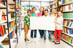Kinder, die Weißbuchblatt in der Bibliothek halten Stockfotos