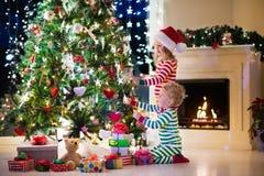 Kinder, die Weihnachtsbaum verzieren lizenzfreie stockbilder