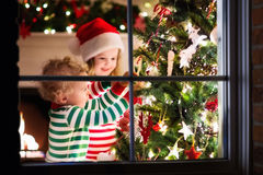 Kinder, die Weihnachtsbaum verzieren stockfotografie