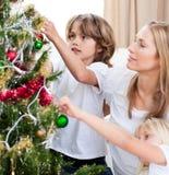 Kinder, die Weihnachtsdekorationen hängen Lizenzfreies Stockbild