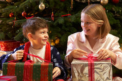Kinder, die Weihnachtsgeschenke öffnen Stockfotos