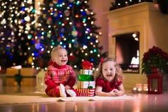 Kinder, die Weihnachtsgeschenke am Kamin öffnen Stockbild