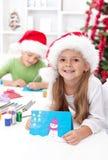 Kinder, die Weihnachtsgrußkarten bilden Stockfotografie