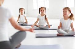Kinder, die Yoga in einer Lotoshaltung mit Lehrer üben stockfotos