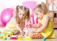 Kinder, die zu Hause hölzerne Spielwaren spielen Lizenzfreies Stockbild