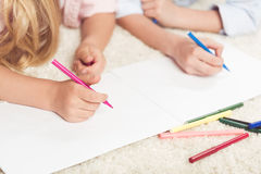Kinder, die zu Hause mit Filzstiften auf Blatt des leeren Papiers schreiben Lizenzfreie Stockfotos