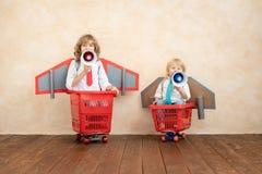 Kinder, die zu Hause mit Raketenrucksack spielen stockfotografie