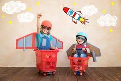 Kinder, die zu Hause mit Raketenrucksack spielen lizenzfreie stockbilder