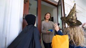 Kinder, die zum Nachbarhaus für Bonbons auf Halloween, Trick-oder-behandelnd gehen lizenzfreie stockbilder