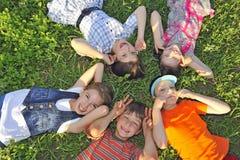 Kinder, die zusammen auf dem Boden legen Stockbild