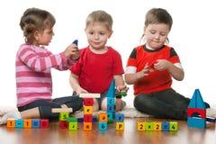 Kinder, die zusammen auf dem Fußboden spielen Lizenzfreies Stockfoto