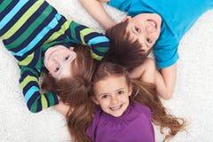 Kinder, die zusammen auf den Fußboden legen Stockbild