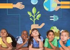 Kinder, die zusammen denken und blaue Wand mit der Wiederverwertung und den auswechselbaren Grafiken Lizenzfreie Stockfotos