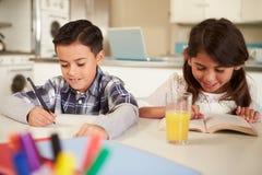 Kinder, die zusammen Hausarbeit bei Tisch tun Stockbilder