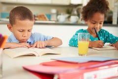 Kinder, die zusammen Hausarbeit bei Tisch tun Stockfotografie