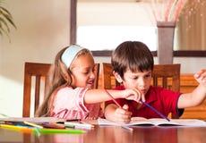 Kinder, die zusammen Heimarbeit tun Stockbild