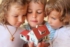 Kinder, die zusammen im Handbaumuster des Hauses halten stockfotografie