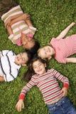 Kinder, die zusammen im Klee mit Köpfen liegen Lizenzfreies Stockbild