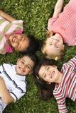 Kinder, die zusammen im Klee mit Köpfen liegen Stockfotos