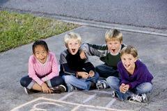 Kinder, die zusammen lachen auf Fahrstraße sitzen Lizenzfreies Stockbild