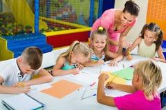 Kinder, die zusammen mit Tutor an der Hobbygruppe zeichnen Stockfoto