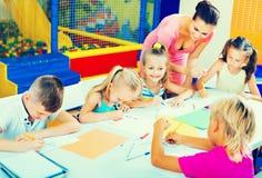 Kinder, die zusammen mit Tutor an der Hobbygruppe zeichnen Stockbilder