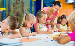 Kinder, die zusammen mit Tutor an der Hobbygruppe zeichnen Lizenzfreies Stockfoto